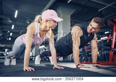 Man And Woman Strengthen Hands At Fitness Training. Fitness Young People Doing Pushups In A Gym Look
