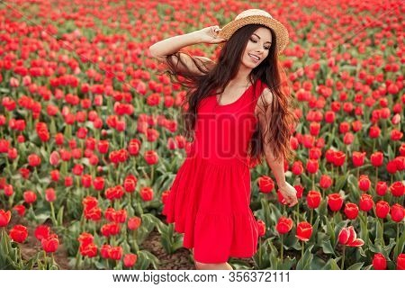 Charming Carefree Young Long Haired Brunette In Red Sundress And Straw Hat Enjoying Nice Day While S