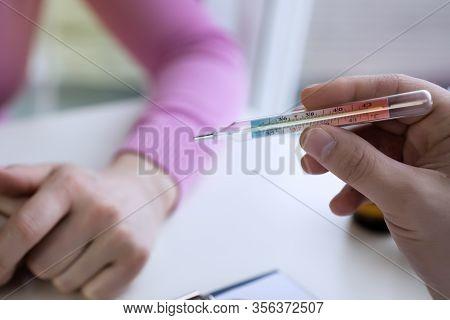 Closeup Shot Of A Woman Looking At Thermometer.