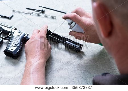 A Man Lubricates A Gun. A Man Is Cleaning A Gun. Oil For Weapons.