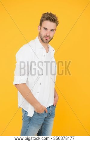 In His Style. Serious Man In Jeans Yellow Background. Fashion And People Concept. Sexy And Handsome.