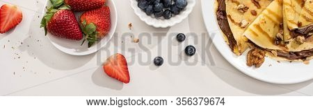 Top View Of Tasty Crepes With Chocolate Spread And Walnuts On Plate Near Bowls With Blueberries And