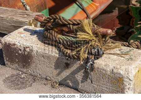 Frayed And Taped Line Securing Fishing Boat To Wharf
