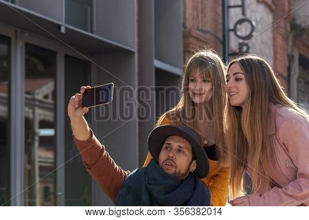 Young Man In A Wheelchair Taking A Selfie With A Mobile Together With Two Young Girls