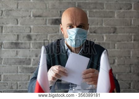 Man In Medical Mask Putting His Vote To Voting Ballot Box.