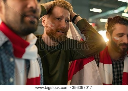 Soccer fans feeling disappointed on seeing favourite team lose the match. Group of disappointed supporter wearing scarf and paint on face upset. Football fans with team's flag upset about losing game.