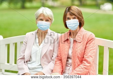 health, safety and pandemic concept - two senior women or friends in medical masks for protection from virus sitting on bench at summer park