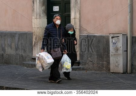 Catania, Italy- March 12, 2020: Coronavirus in Italy. Unidentified people wearing protective masks