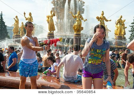 """MOSCOW - JULY 14: Young people shooting and throwing water at each other during flash mob """"Water Battle"""" near People??s Friendship Fountain in VDNKH on July 14, 2012 in Moscow."""