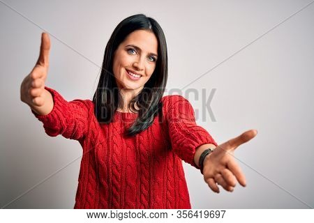 Young brunette woman with blue eyes wearing casual sweater over isolated white background looking at the camera smiling with open arms for hug. Cheerful expression embracing happiness.