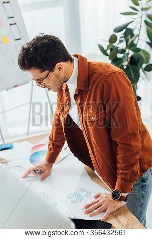 Selective Focus Of Ux Developer Looking At Wireframe Sketches Of Ux Design Near Computer On Table In