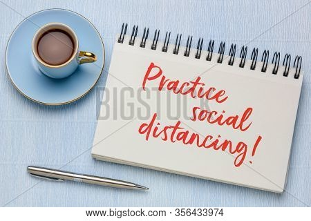 practice social distancing advice or reminder - handwriting in a spiral art sketchbook with a cup of coffee, infection control during covid-19 virus pandemic
