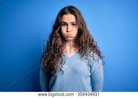 Young beautiful woman with curly hair wearing blue casual sweater over isolated background puffing cheeks with funny face. Mouth inflated with air, crazy expression.