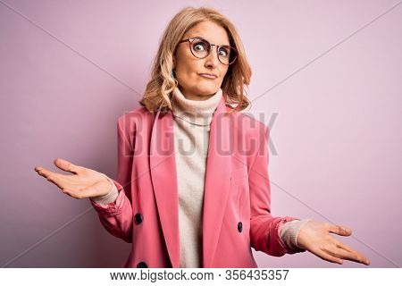 Middle age beautiful blonde business woman wearing elegant pink jacket and glasses clueless and confused expression with arms and hands raised. Doubt concept.