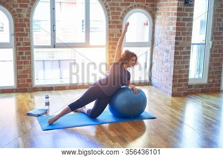 Middle age beautiful sportswoman doing exercise using fitness ball in a class of yoga at gym
