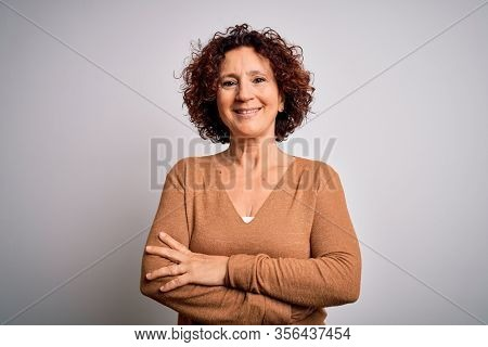 Middle age beautiful curly hair woman wearing casual sweater over isolated white background happy face smiling with crossed arms looking at the camera. Positive person.