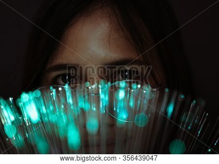 Diverse Asian Girl Looks Through Futuristic Teal Coloured Bokeh - Millennial Woman Looking At Camera