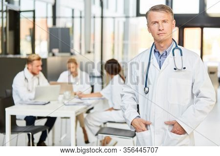 Doctor as head physician with authority and competence stands confidently in front of his team
