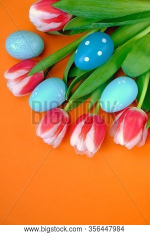 Easter Holiday. Decorative Blue Easter Eggs In Tulip Flowers On A Bright Orange Background.spring Ho