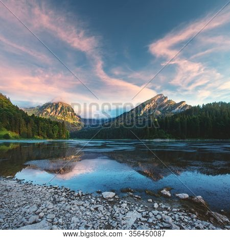 Peaceful summer view on Obersee lake in Swiss Alps. Sunrise sky and mountains reflections in clear water. Nafels village, Switzerland. Landscape photography
