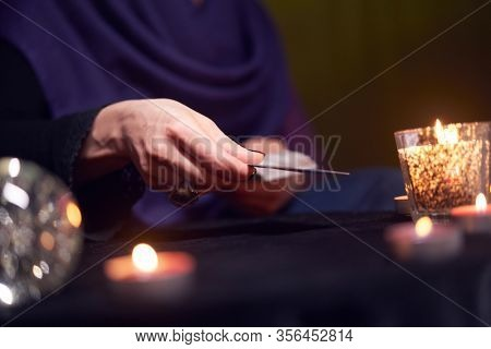 Fortuneteller female divines on cards sitting at table with burning candles
