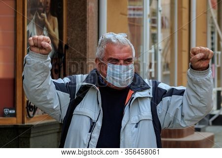 Uzhgorod, Ukraine - March 18, 2020: A Man In A Medical Mask In The City Center Calls For Optimism Du