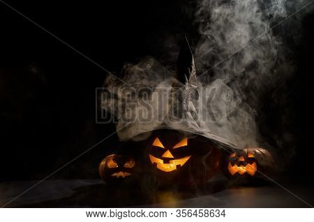 Three Creepy Halloween Grinning Pumpkins Glow In The Dark Among The Fog. Jack-o-lantern In A Witch H