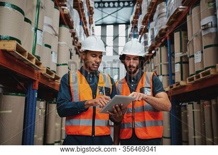 Focused Manager And Employee Standing In Warehouse Discussing Inventory Stock While Standing Between