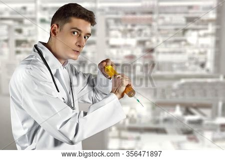 An Angry Doctor With A Big Syringe In His Hands. Bad Medic. Concept Of Young Inexperienced Doctor. M