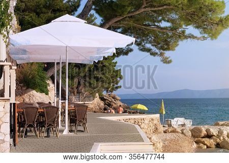 White Beach Umbrellas, Tables And Chairs For Relax And Comfort On Terrace Of Cafe On Sea Coast. Happ