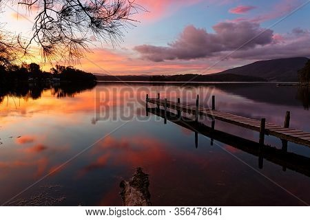 Scenic Sunset And Beautiful Reflections On Wallaga Lake With Old Timber Jetty In View.  Australia
