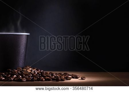 Black Disposable Cup Of Coffee With Smoke And Scattered Coffee Beans On Dark Background. Space For T