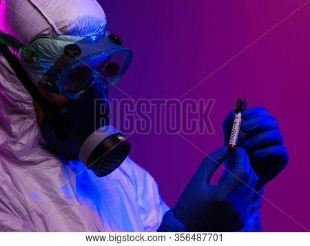 Coronavirus, Doctor holding positive covid-19 virus Blood Sample tube. Wearing biohazard epidemic Protective mask, suit and glows.