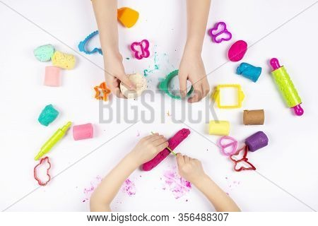 Little Girls Hands Playing With Colorful Modeling Clay On White Background. Educational Game With Cl