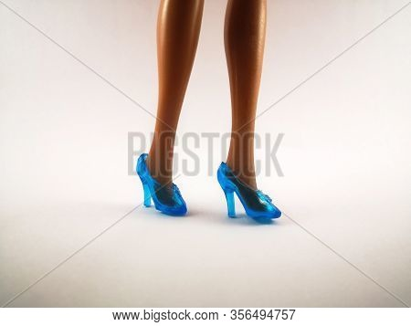 Blue High Heel Shoes Dressed On Barbies Legs On An Isolated Background