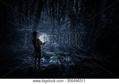 Boy holding moon at night in the forrest