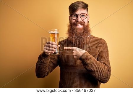 Irish redhead man with beard drinking a glass of refreshing beer over yellow background very happy pointing with hand and finger