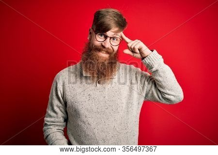 Handsome Irish redhead man with beard wearing casual sweater and glasses over red background Smiling pointing to head with one finger, great idea or thought, good memory
