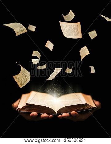 Man Is Holding Book With Flying Pages And Radiance Light On Black Background. Learing, Reading, Know