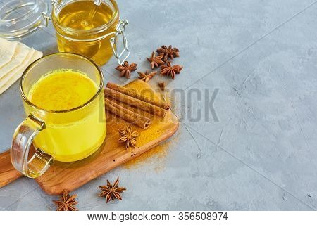 Golden Milk In A Transparent Glass Cup. Curcumin, Anise, Cinnamon Virus Protection. The Concept Of H