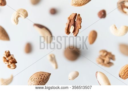 Assorted Nuts Flying Above White Background, Levitation Effect