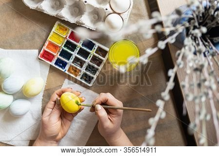 Young Blonde Woman Painting Eggs With Watercolors Preparing For Easter Celebration