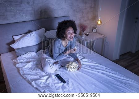 Beautiful Mixed Race Woman Wearing Pajamas Sitting On Bed, Eating Popcorn And Watching A Comedy Movi