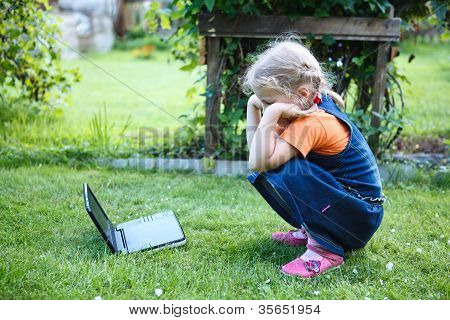Little Interested Girl Watching Dvd Movies On Device In Green Lawn