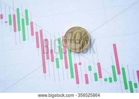 Ten Rouble Coin On Currency Graph. Exchange Rate Chart. Ruble Depreciation. Exchange Rate Of Rouble