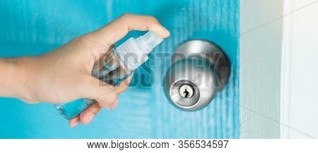 Woman Hand Spraying Alcohol Sanitizer Bottle To The Doorknob, Against Novel Coronavirus Or Corona Vi