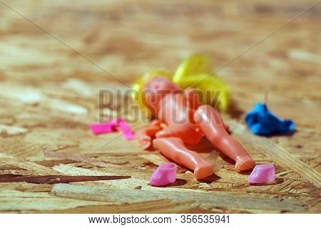 Doll Body Parts On A Wooden Background. Copy Space. Top View