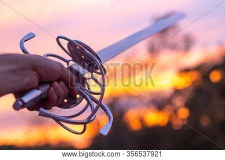 A Hand Thrusting A Large Rapier Sword Against A Sunset Sky