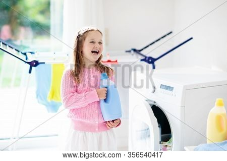 Child In Laundry Room With Washing Machine Or Tumble Dryer. Kid Helping With Family Chores