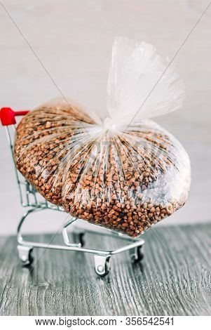 Packet Of Dry Buckwheat In Small Supermarket Pushcart Closeup. Concept Of Consumer Panic About Coron